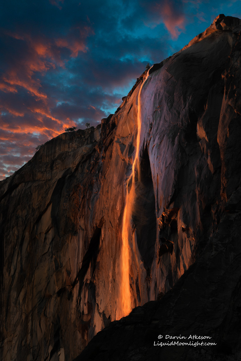 Cold days in the middle of Winter doesn't always draw a lot of people to Yosemite Valley.  The one exception is a short lived phenomenon in which the shadow of El Capitan sweeps across the face of the cliffs to align perfectly with Horsetail Fall causing the waterfall to glow in the dazzling colors of the setting sun.   The effect gives the impression of falling lava or fire reminiscent of Yosemite's famous Firefall where hot glowing embers were pushed off the cliffs of Glacier Point creating literally falling fire that could be seen from the valley floor.   The Firefall event was discontinued in 1968 by the National Park Service in part due to huge crowds it drew and that it was not a naturally occurring event.    But sometimes nature is more clever than we think and had been having its own version of Firefall each February for thousands of years but it wasn't really noticed until 1973 when photographer Galen Rowell snapped his now famous photograph of Horsetail Fall glowing in the evening sun.   Since that time each February photographers and nature lovers have been flocking to Yosemite to witness the natural version.    The event has become so popular that the National Park Service now sections of areas to accommodate special parking.   As is often the case with nature, the show varies from day to day and year to year and even minute to minute.   Weather can make or break the event and as often is the case it may not occur at all.    Clouds cause many to give up early and head down the long road for home only to have the sun pop out at the last minute creating fantastic light that lasts  just a few minutes and then is gone.   Drought in California made this year very questionable but a bit of snow and a last minute rainstorm caused the fall to spring to life.   If you arrive early Horsetail Fall may be barely flowing but as the sun warms the High Sierra, the snow melts and the waterfall's flow picks up.  So be sure to stick it out to the last minute.  Thi