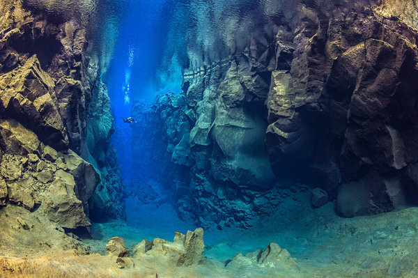 A diver explores the cathedral at Silfra canyon, a deep fault filled with fresh water in the rift valley between the Eurasian and American tectonic plates) at Thingvellir National Park, Iceland. In this photo the American plate is on the left and the Eurasian plate on the right. Model released.